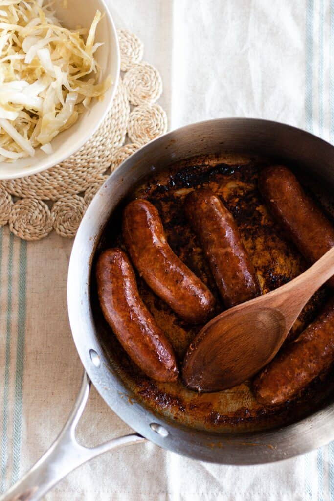 pan fried sausage in a skillet with a bowl of sauerkraut in the background