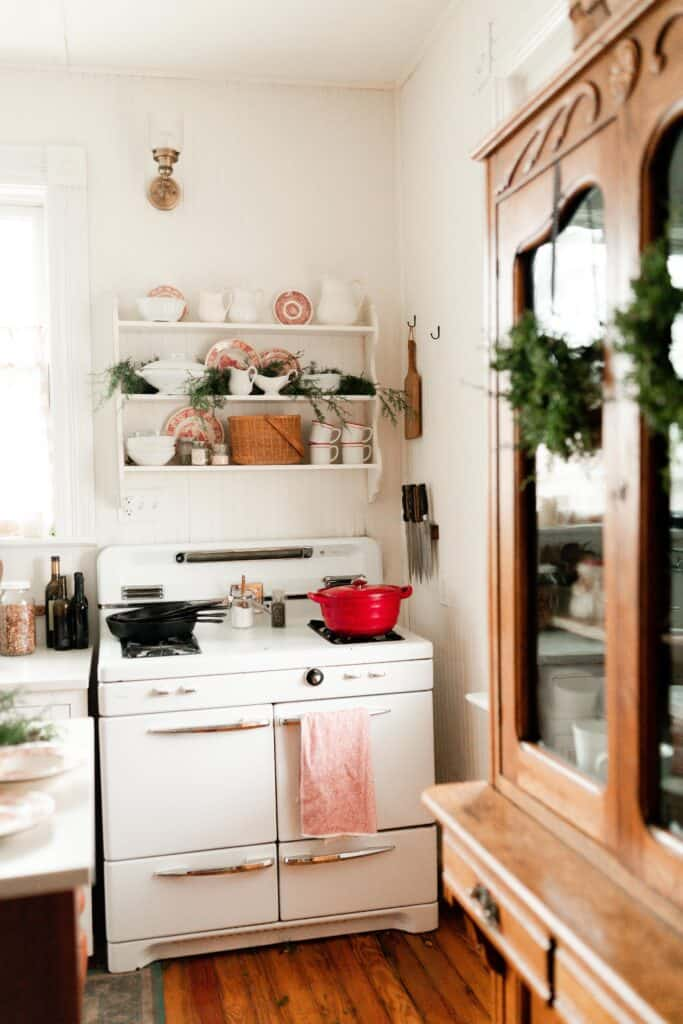 antique stove with pops of red decor on the open shelves
