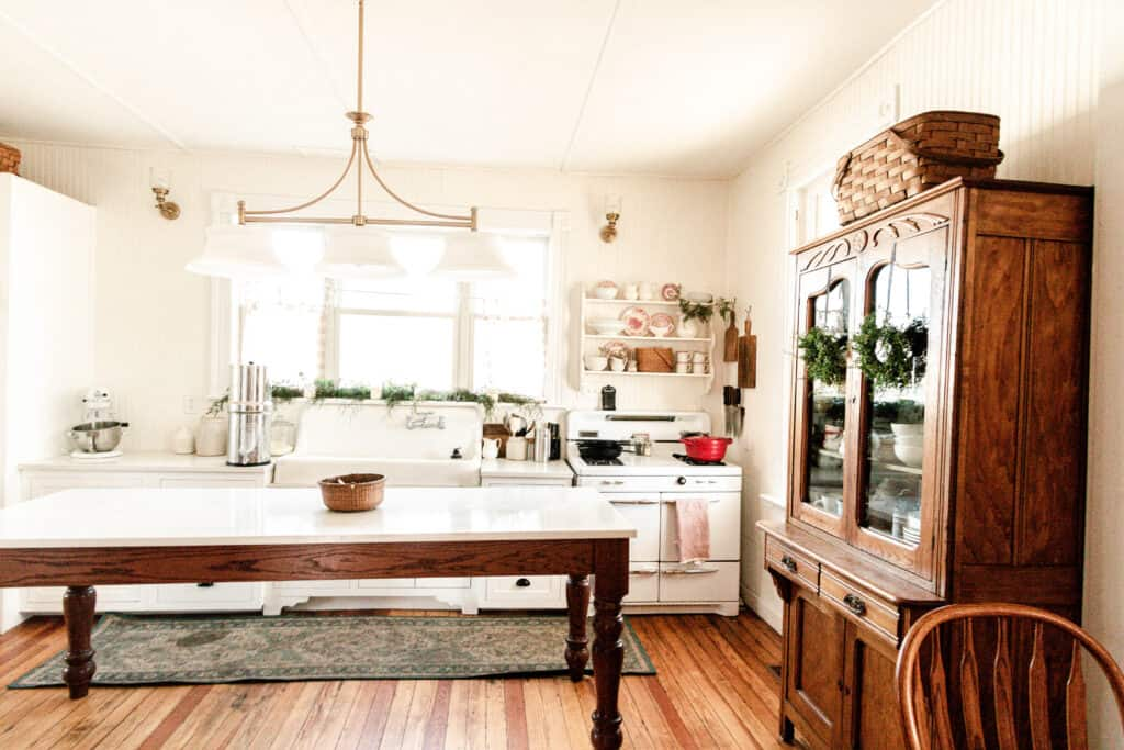 farmhouse kitchen decorated for Christmas with greenery and pops of red