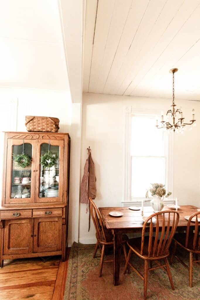 eat-in kitchen with wreaths hanging with ribbon from a vintage China cabinet, a red and white checked apron hung on the wall and a table set with red and white plates
