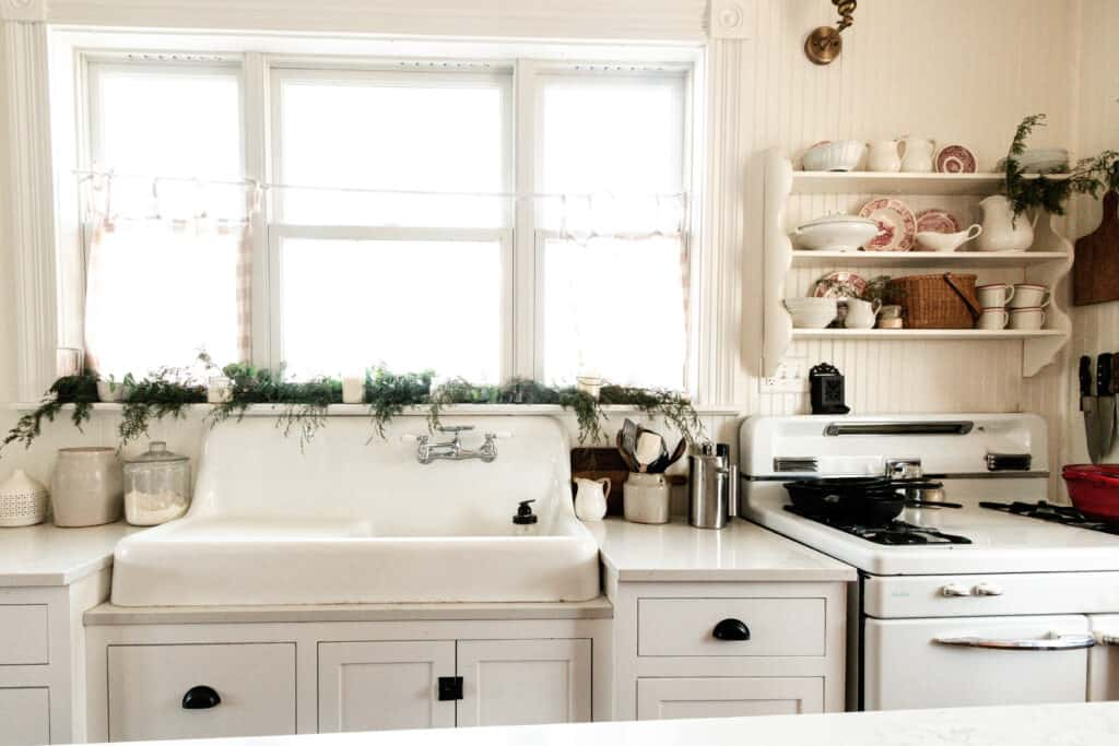 white farmhouse kitchen decorated for Christmas. Garland sits on the window sill, red and white plates and mugs are nestled on a an antique shelf