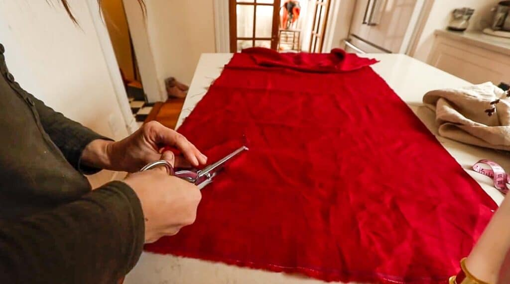 women cutting red linen fabric