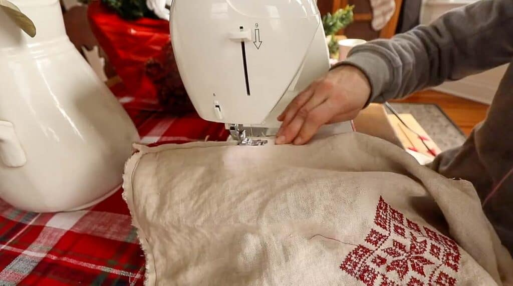 sewing a DIY Christmas pillow together at a sewing machine