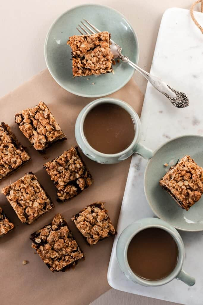 overhead photo of date squares on parchment paper with two mugs of coffee.