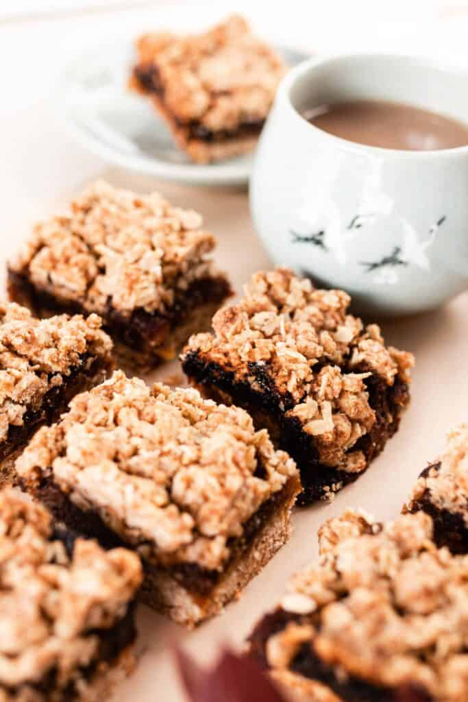 date squares on parchment paper with a mug of coffee behind