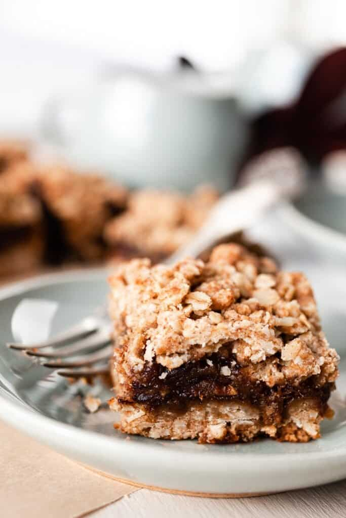 healthy date bar with oats on a soft green plate with a fork
