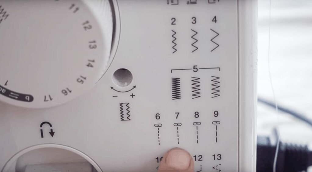 finger pointing to sewing machine stitch options