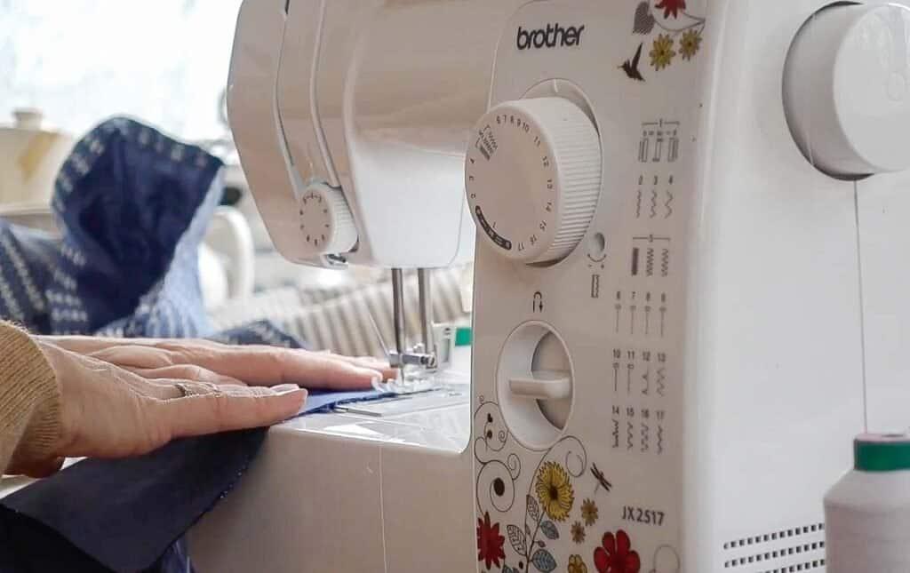 women guiding fabric through a sewing machine to create a seam