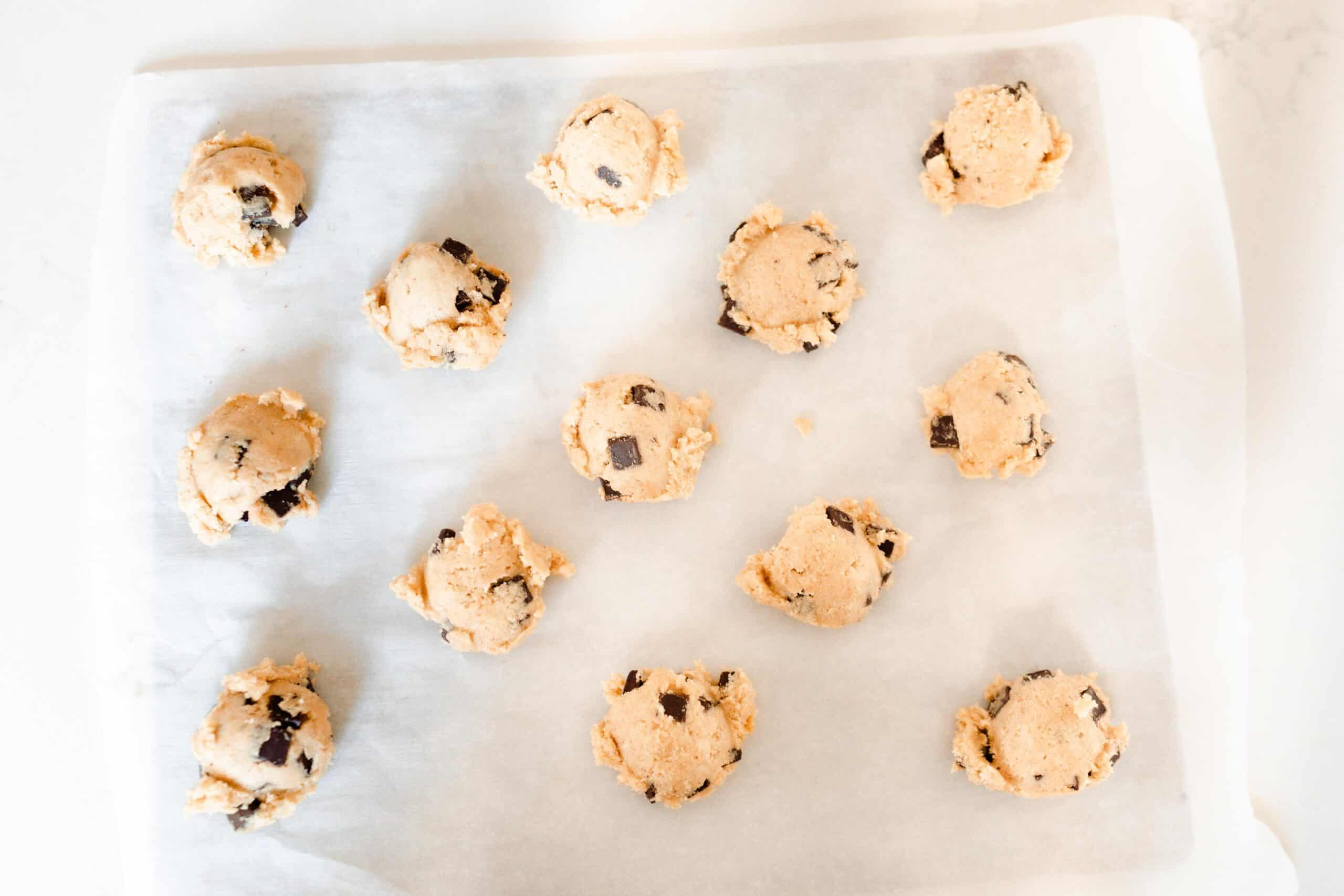 sourdough chocolate chip cookie dough balls on a parchment lined baking sheet