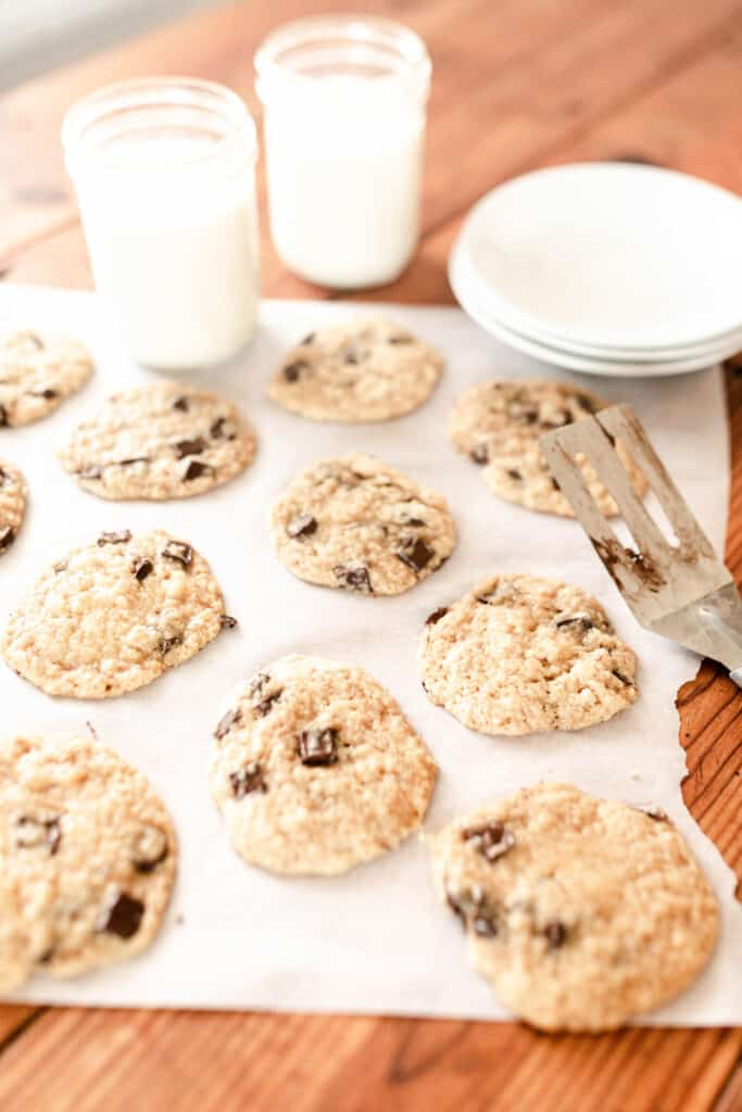 sourdough cookies on parchment paper with glasses of milk ad plates in the back