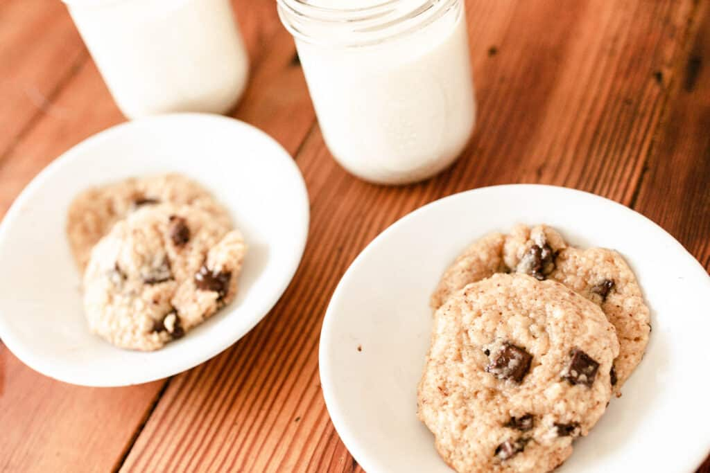 two white bowls of sourdough chocolate chip cookies with glasses of milk in the background