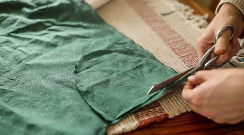 Women cutting out green fabric