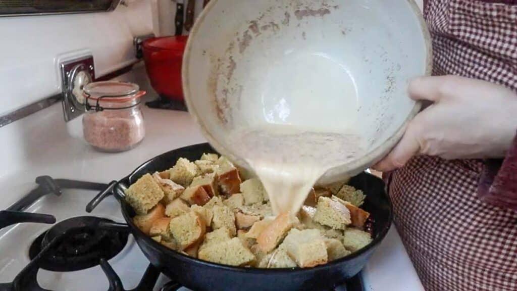 pouring custard over sourdough bread in a cast iron skillet