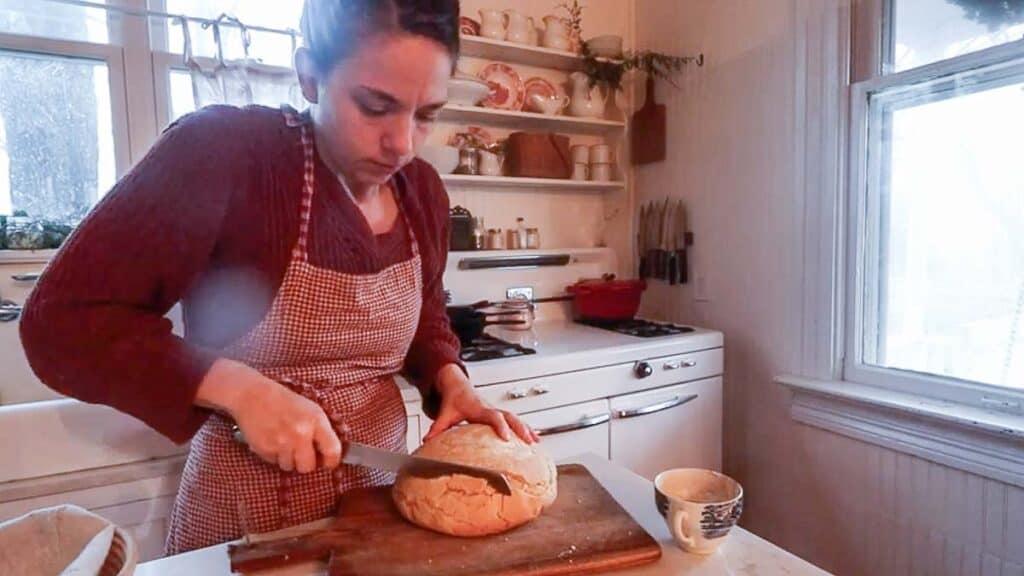 women slicing bread on a cutting board.
