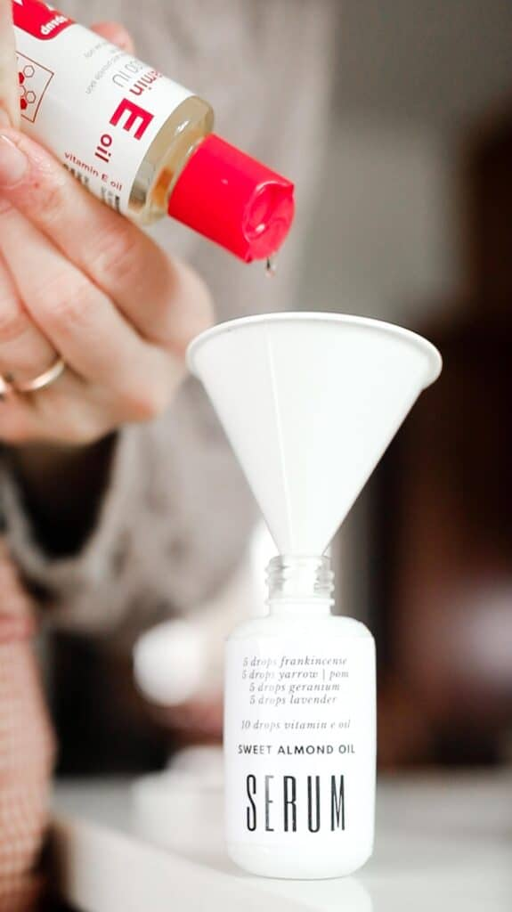 vitamin e oil being poured into a white bottle