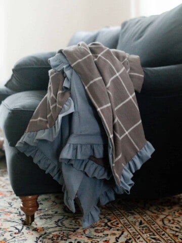 DIY flannel blanket with a ruffle on a blue couch