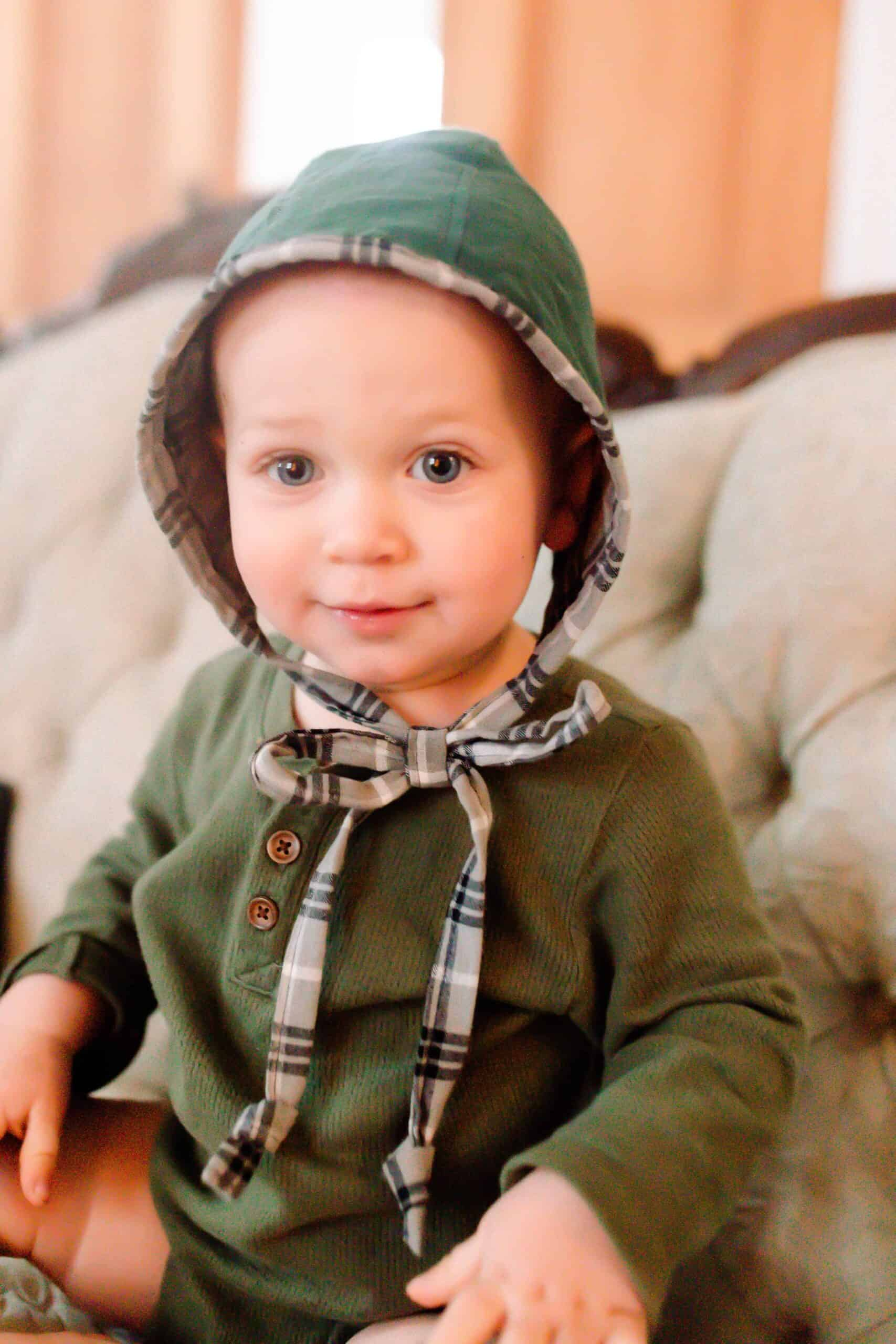 Baby boy in a green shirt wearing a green and plaid homemade bonnet
