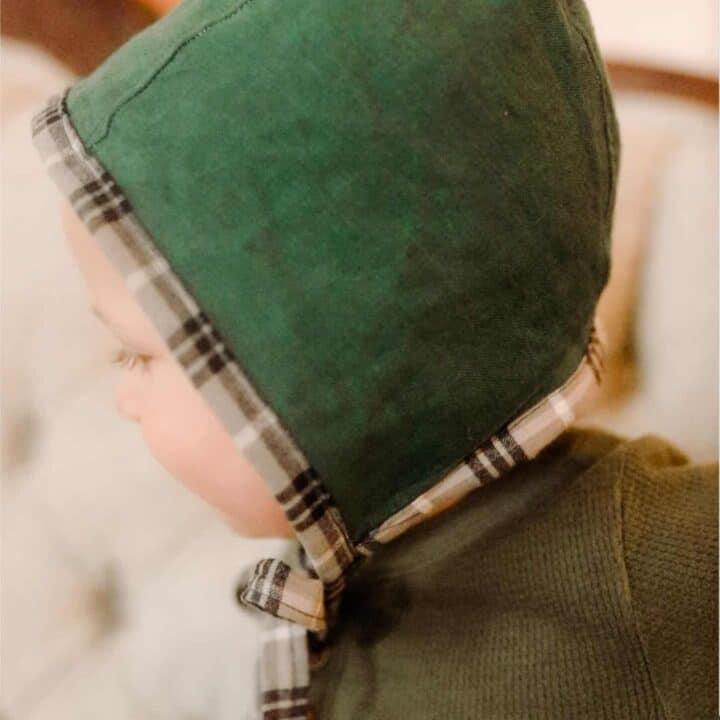 boy wearing a green homemade baby bonnet