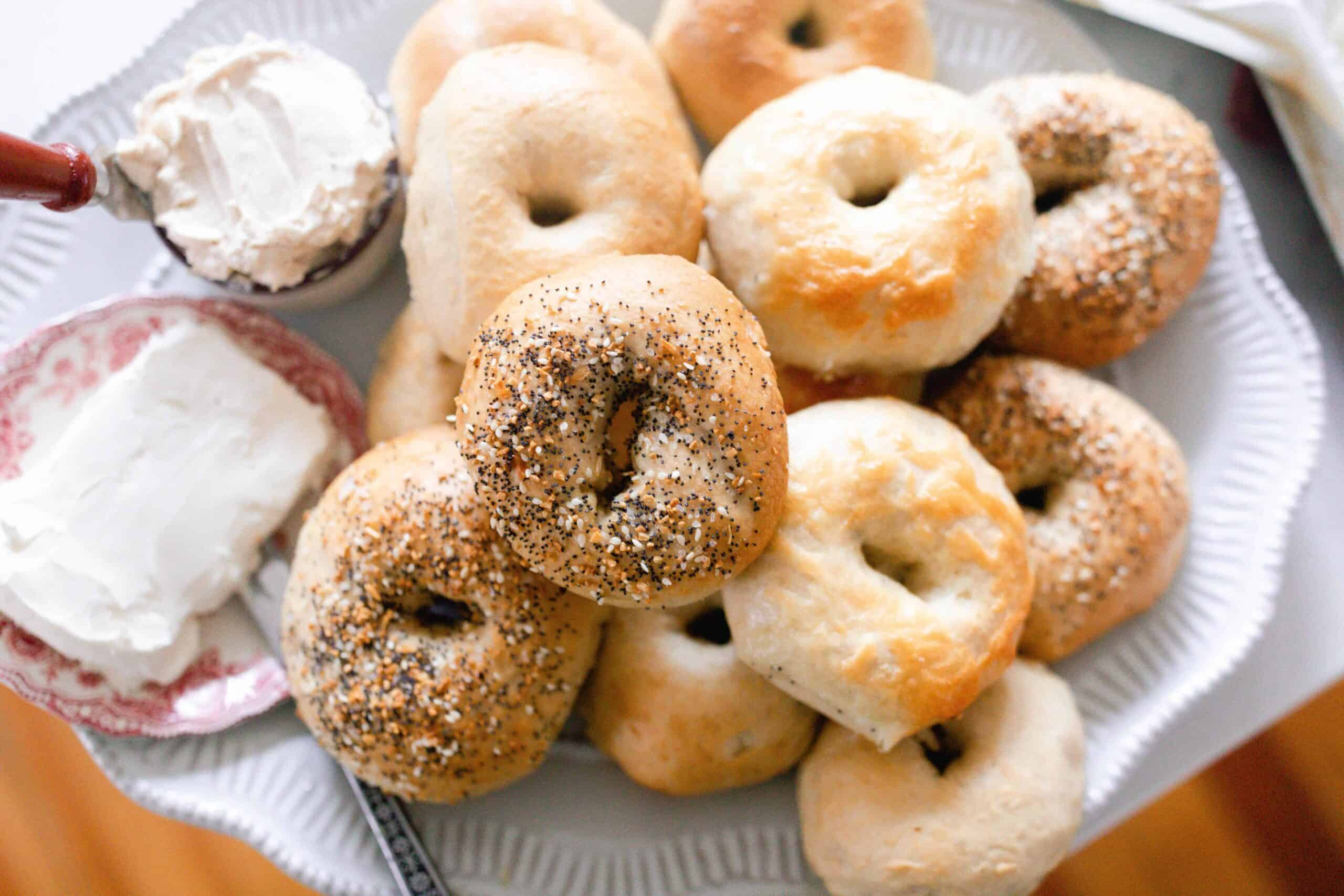 sourdough bagels on a white platter with a cream cheese on a plate