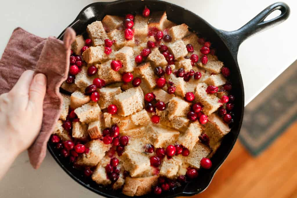 overhead photo of a cast iron skillet with baked French toast casserole with cranberries on top.
