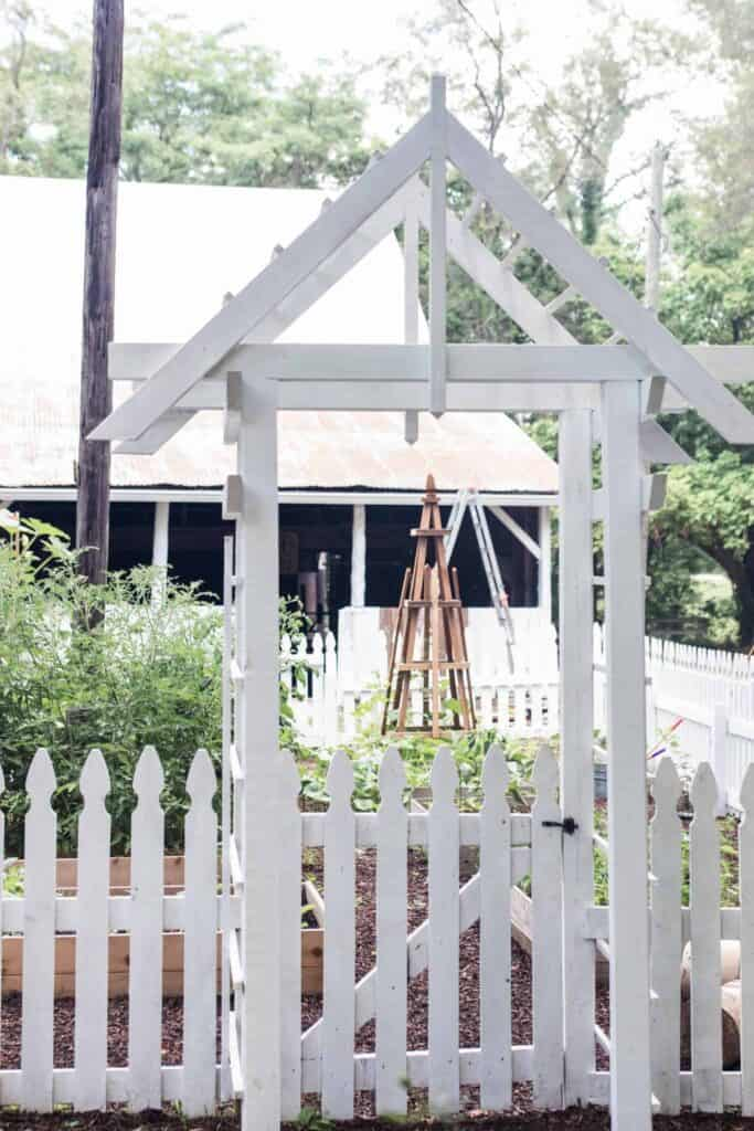 garden entrance with an arbor and a white picket fence - how to start a garden