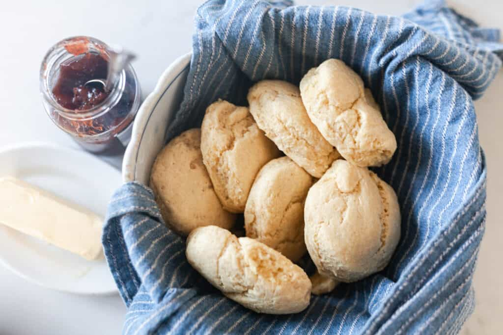 einkorn biscuits in a bowl lined with a blue and white stripped towel with jam and butter to the left