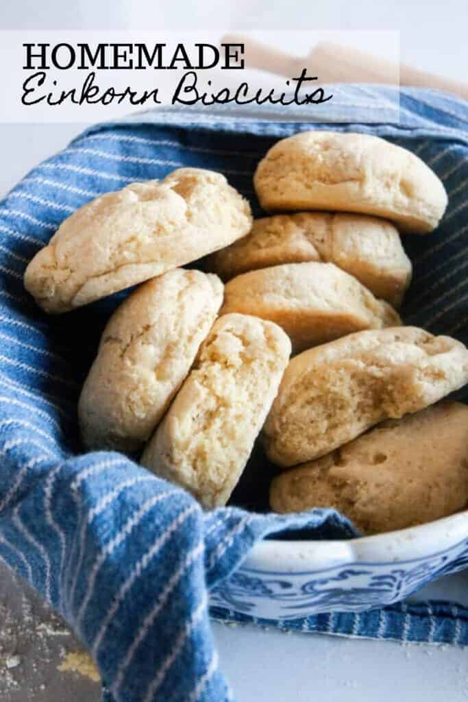 einkorn biscuits in a bowl lined with a blue and white stripped towel and a rolling pin in the background