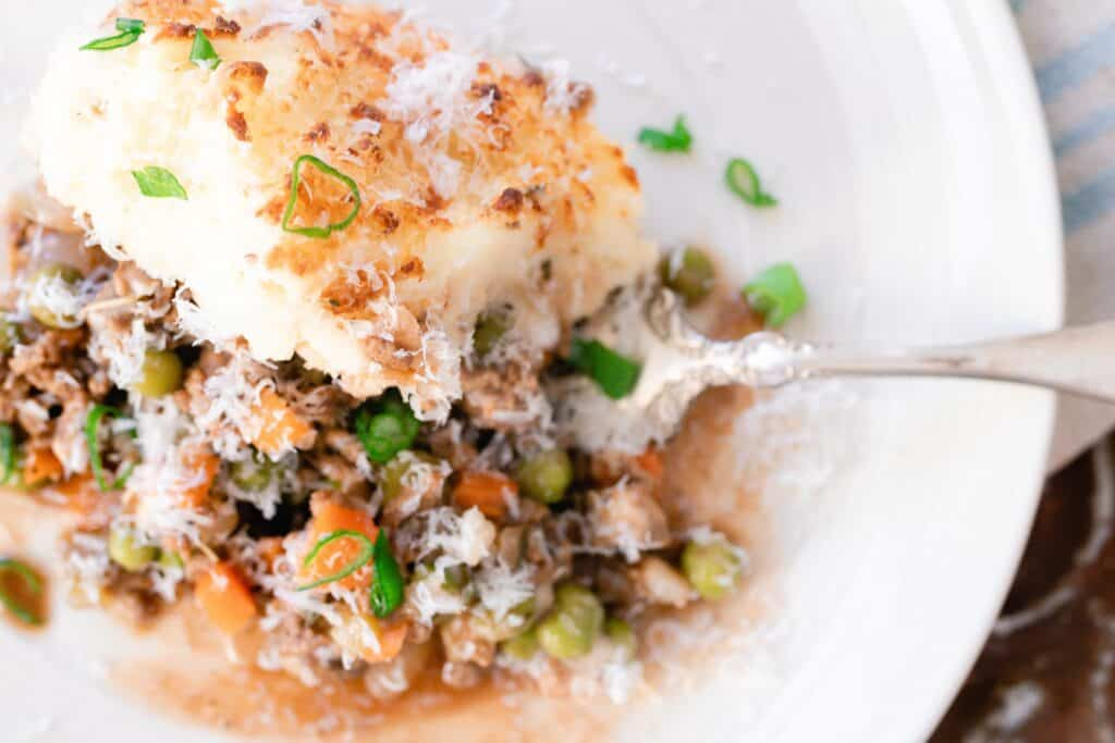 Shepards pie on a plate with an antique spoon
