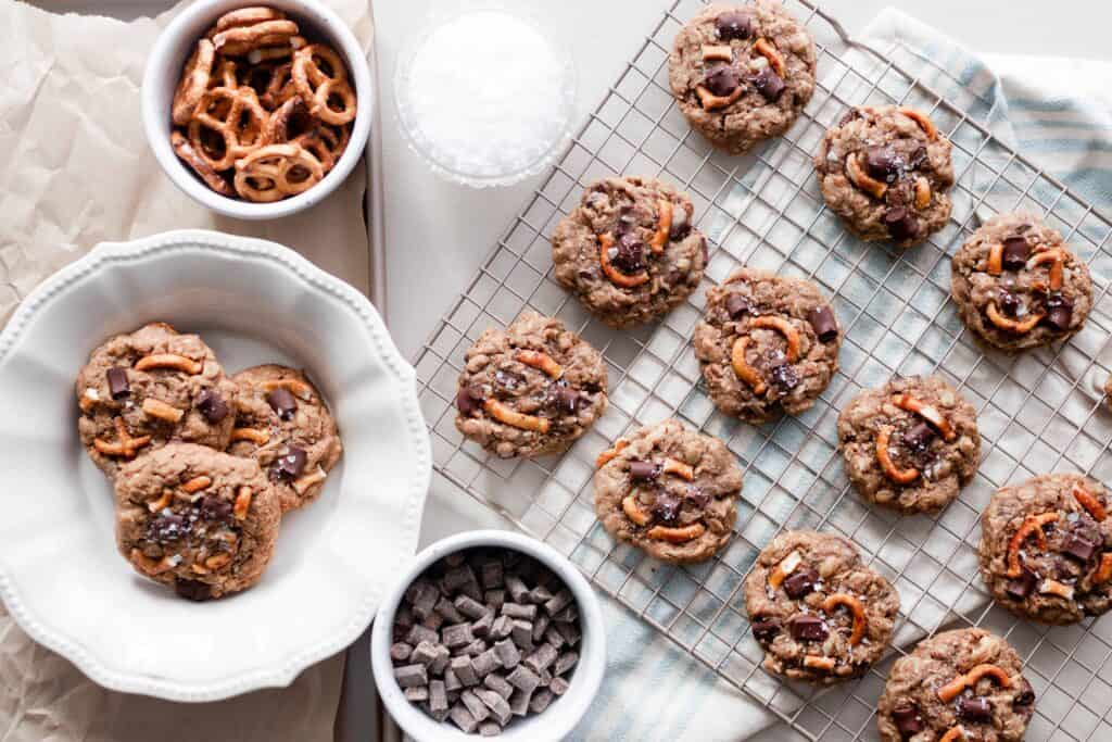 overhead photo of a cooling rack of chocolate oatmeal lactation cookies with a plate of cookies to the left and two white dishes of pretzels and chunks