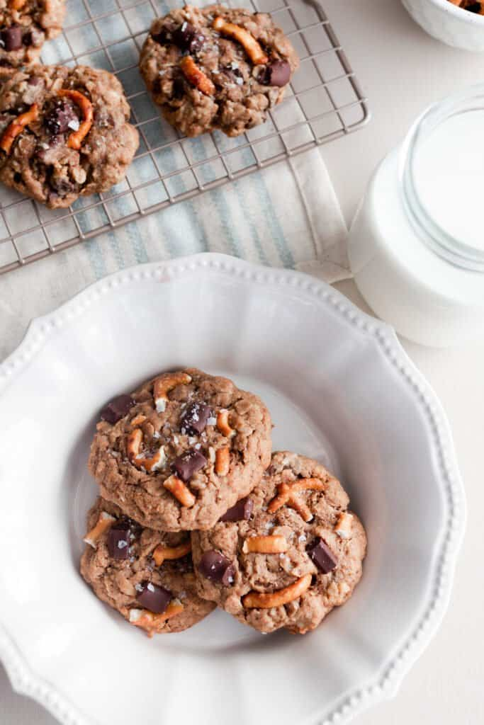 three oatmeal lactation cookies on a white plate with a cooling rack of more cookies behind it