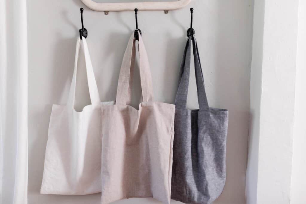 Three DIY linen tote bag hanging on a hook