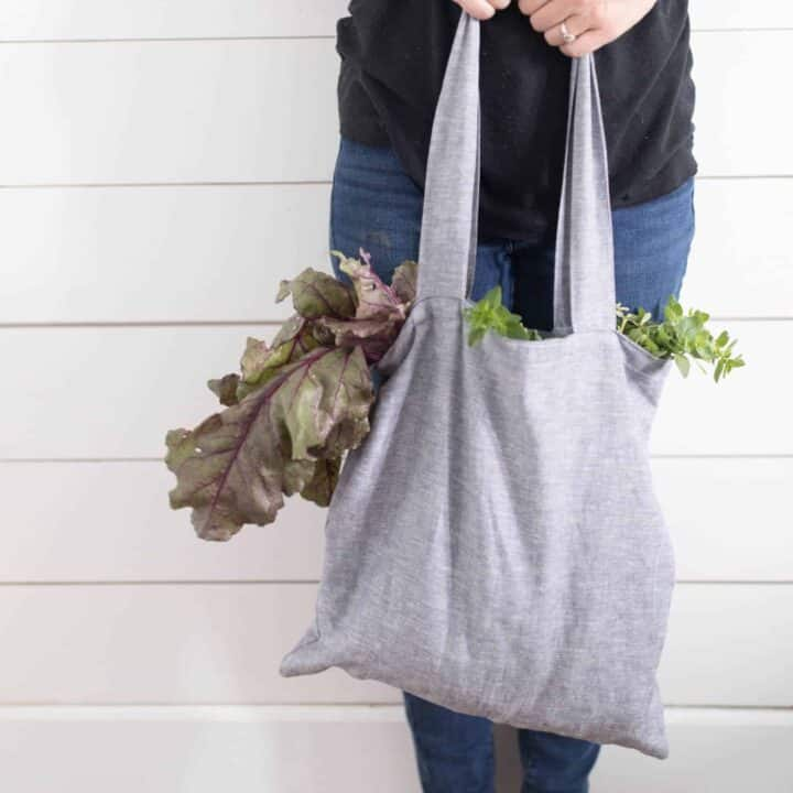 women wearing a black shirt and jeans holding a DIY tote bag full of lettuce