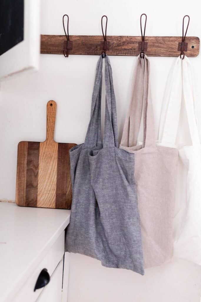 three linen bags hanging on a hook rag in a kitchen