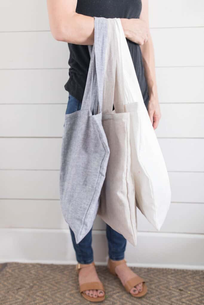 women holding three linen bags on one arm