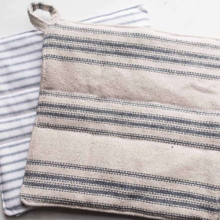 two DIY pot holders made with blue ticking stripe fabric