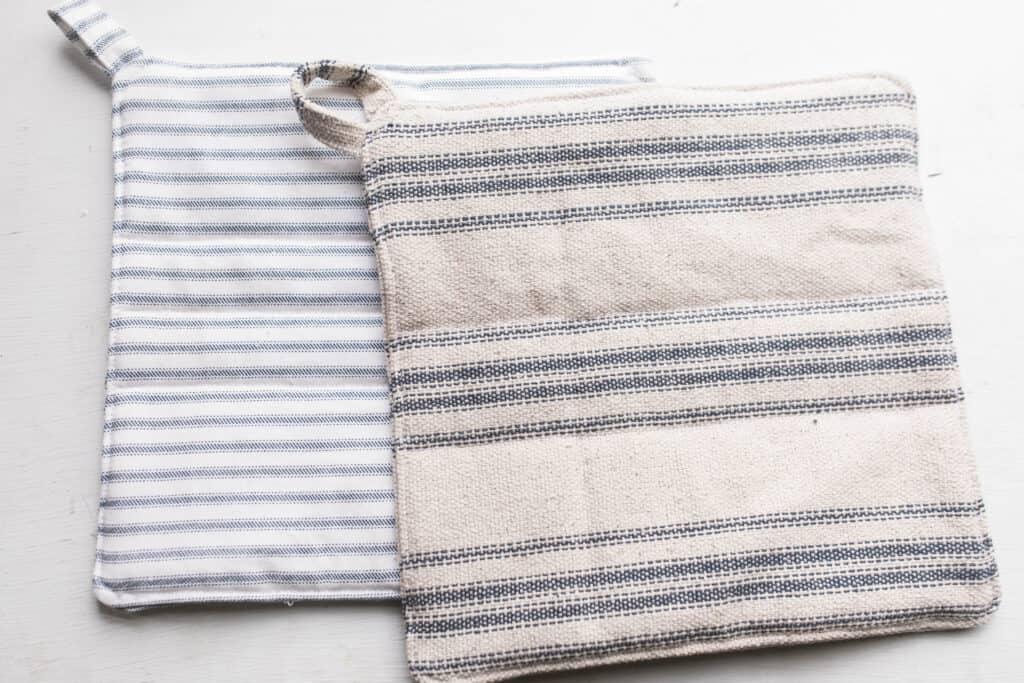 Two homemade pot holders. One blue and white stripped lays on a white table with a blue and cream ticking stripe pot holder on top