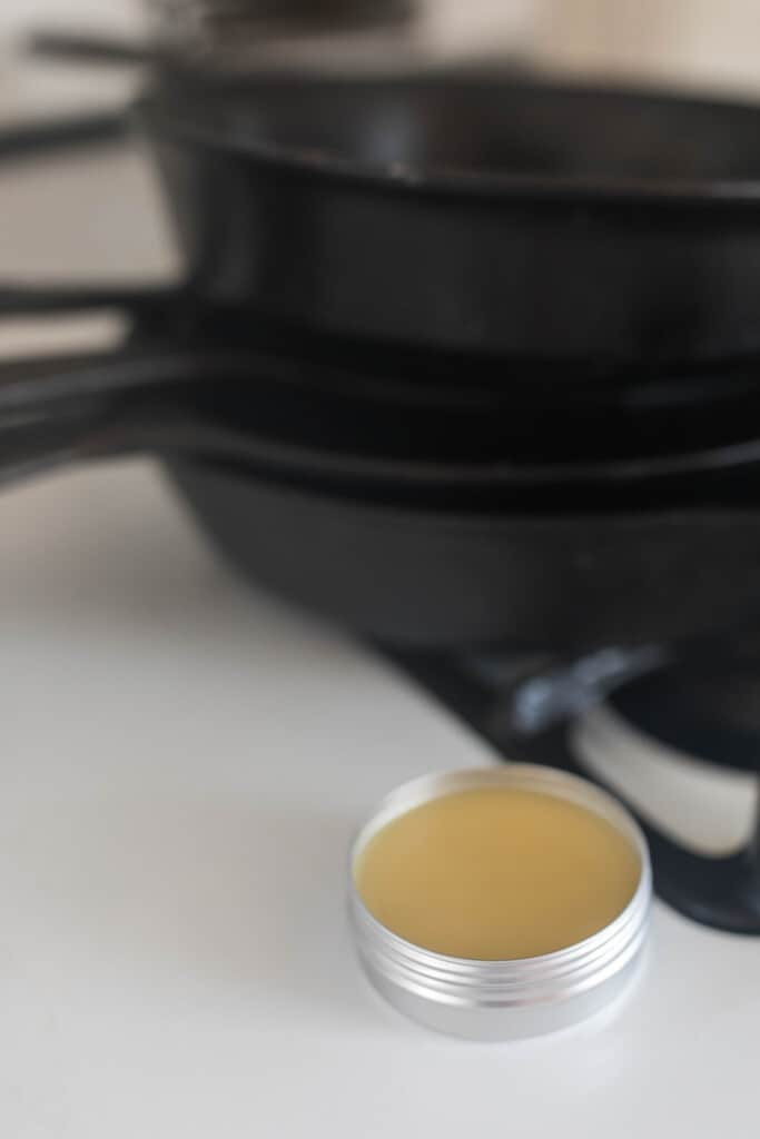 oil seasoning blend in a tin next to cast iron skillet stacked on a stove top