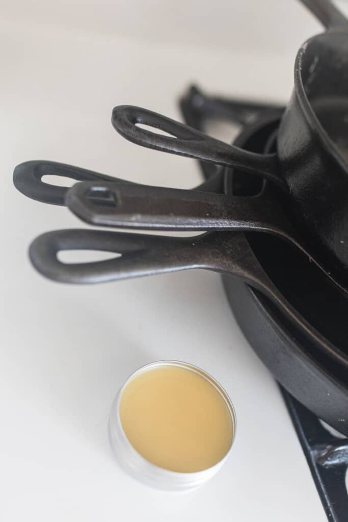 DIy cast iron seasoning oil in a tin next to cast iron skillets stacked on a stove