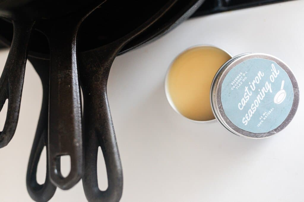 DIY Cast iron seasoning oil in a metal tin with label next to 4 case iron skillet handles