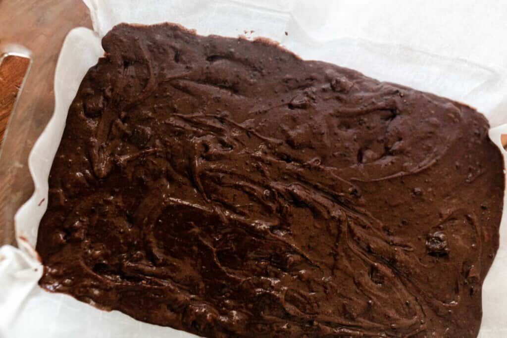 einkorn brownie batter poured into a parchment lined baking dish