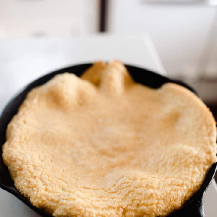 einkorn puff pancake in a cast iron skillet on white quarts countertop. A antique stove is in the background