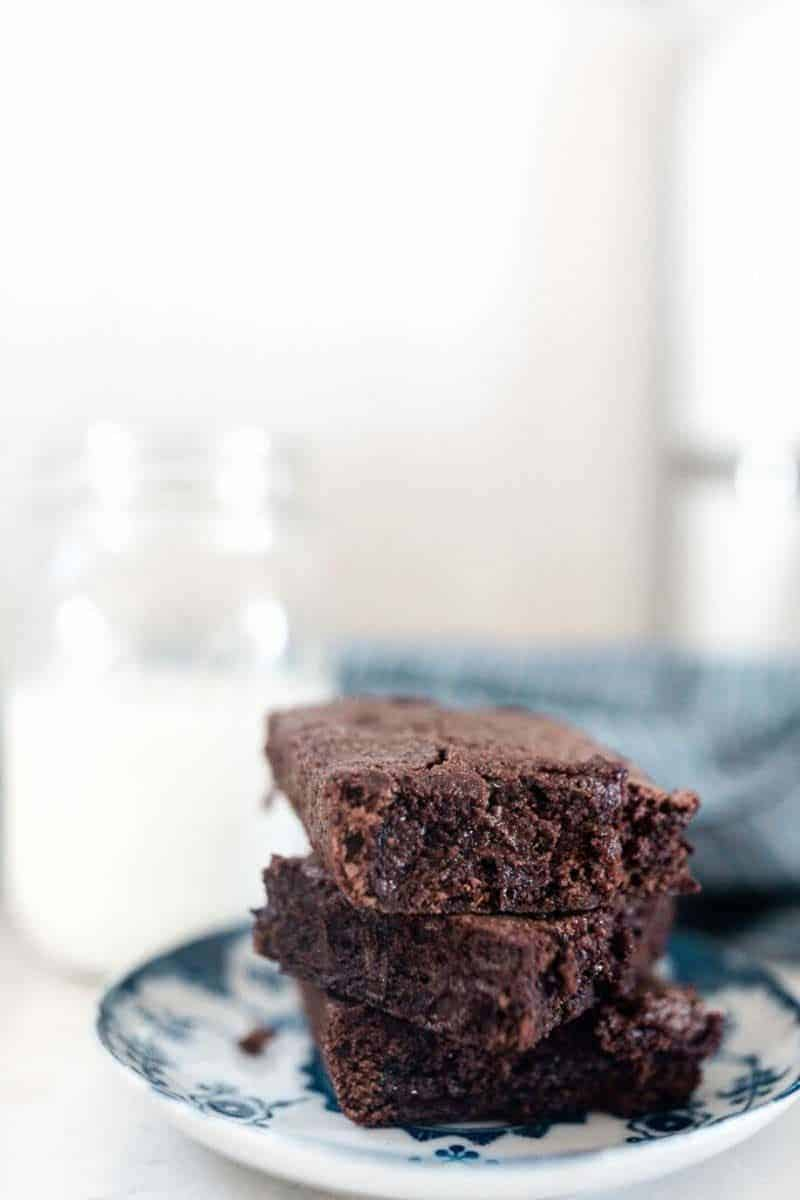 3 einkorn brownies stacked up on a blue and white plate with a glass of milk in the background