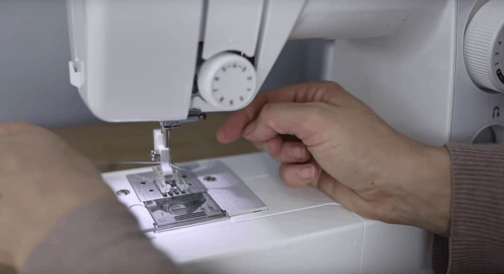 hand putting thread through the needle of a sewing machine