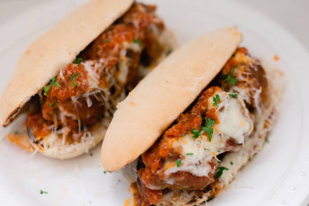 two meatball subs topped with cheese on homemade sourdough sandwich rolls