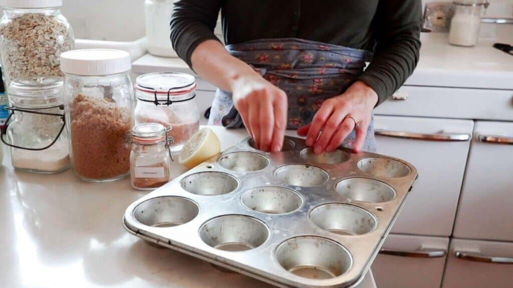 women greasing a muffin tin with her hands