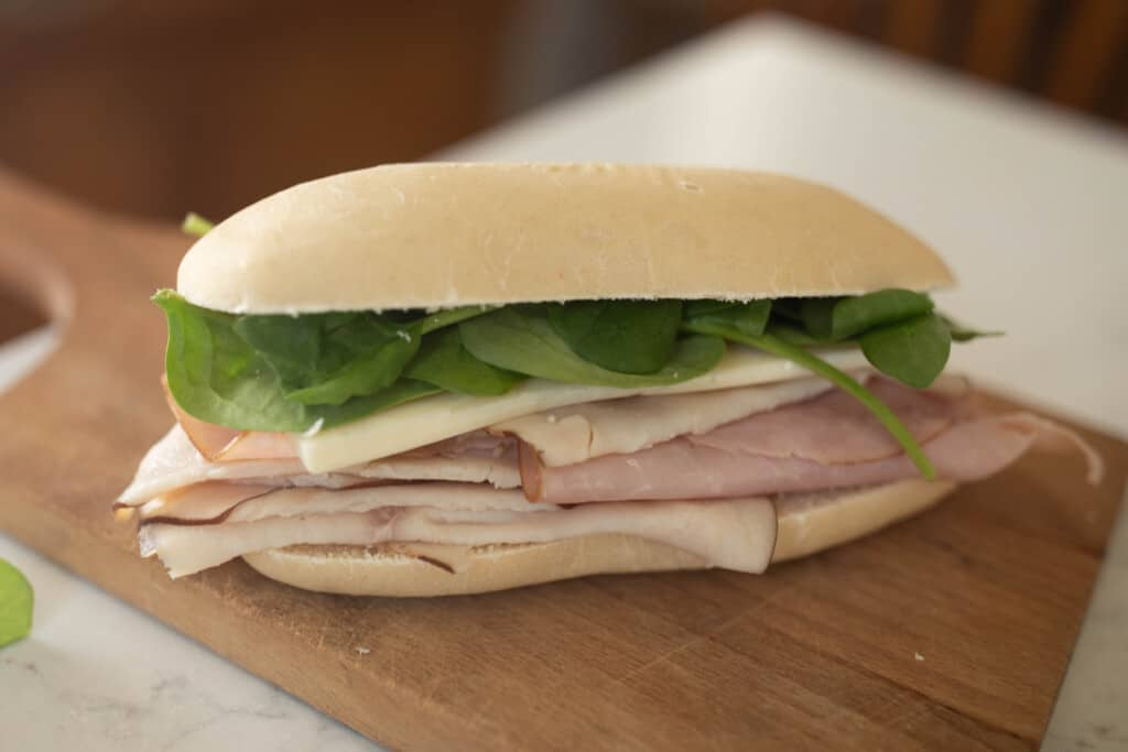 sourdough sandwhich with turkey, ham, cheese and spinach