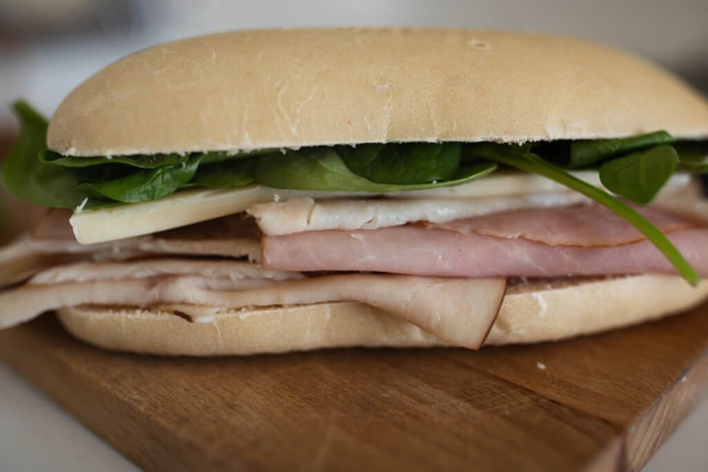sourdough sandwich deli meat, lettuce, and cheese on a wood cutting board
