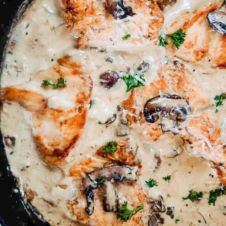 cast iron skillet with seared chicken breast and mushrooms in a cream sauce with fresh herbs on top