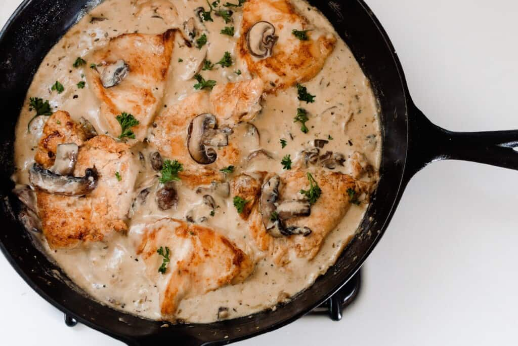 creamy chicken mushrooms sauce in a cast iron skillet topped with herbs