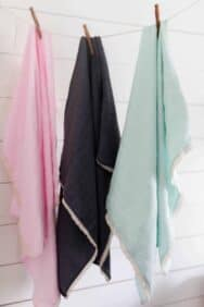 a pink, navy, and teal gauze swaddle blanket with lace hangin with clothespins on string